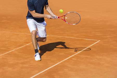 tennis clay: Male tennis player in action on the clay court on a sunny day