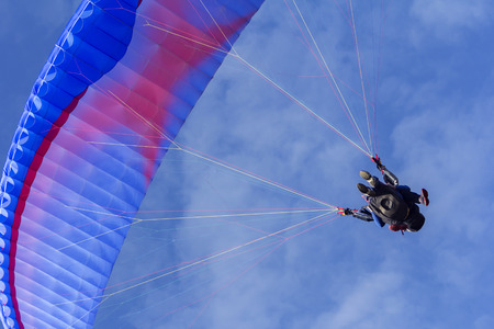 Tandem Paragliding on background of blue summer sky and white clouds