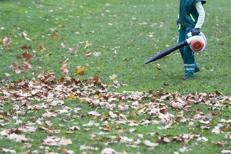 Arbeiter im Park im Herbst sammelt Blätter mit Laubbläser Standard-Bild - 66160832