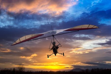 Motorized hang glider flying in the sunset Stock Photo