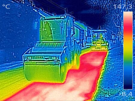 Infrared thermovision image showing Workers on Asphalting paver machine during Road street repairing works Stock Photo