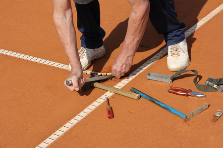Worker Repairing lines on a tennis court Stockfoto