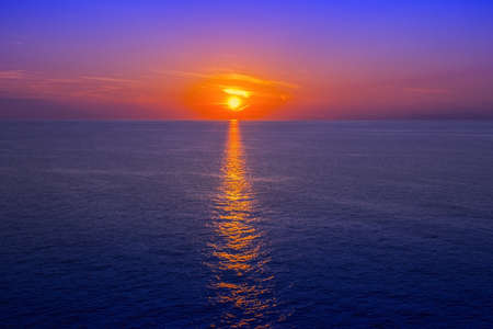 daybreak: Sunset over sea with reflection in water as background