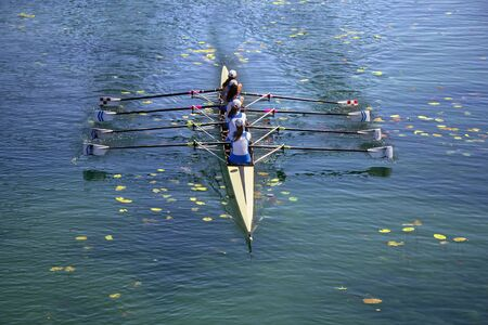Ladies fours rowing team in race on the lake Stock Photo
