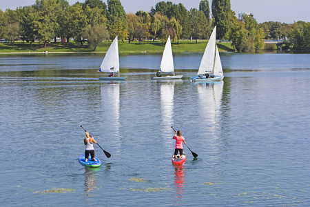 Two women on paddle board and three boat sailling in lake Stock Photo