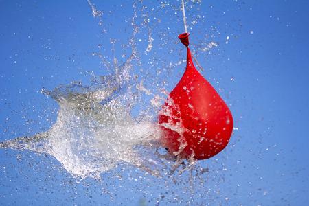Explosion du ballon plein d'eau sur fond de ciel