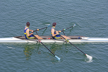 Two young rowers in a racing rower boat