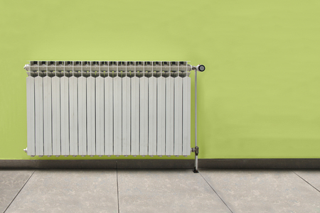 White radiator in front of the green wall