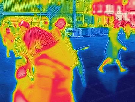 Infrarot-Wärmebild von Menschen, die an einem kalten Wintertag durch die Straßen der Stadt gehen Standard-Bild