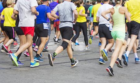 Corredores de maratón corriendo pies de personas de raza en la carretera de la ciudad