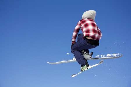 Flying skier at jump inhigh on snowy mountains. Extreme winter sport.