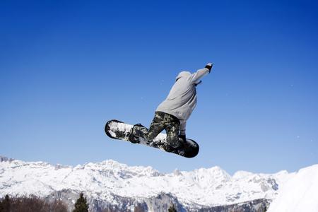 Snowboarder de salto extremo en saltar por encima de las montañas en un día soleado Foto de archivo