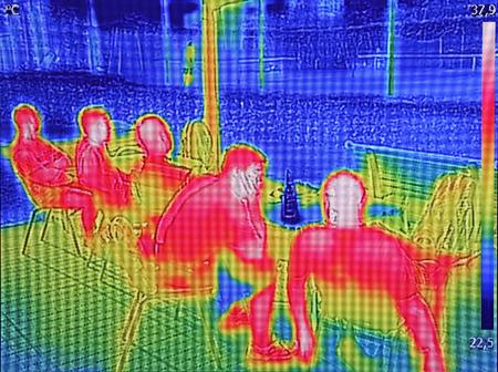 Infrarot-Thermovisionsbild, das zeigt, wenn Leute im Sommer am Tisch sitzen Standard-Bild