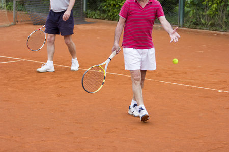 Doubles tennis player with partner in the background