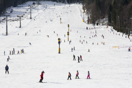 Lots of skiers and snowboarders on the slope at ski resort Standard-Bild