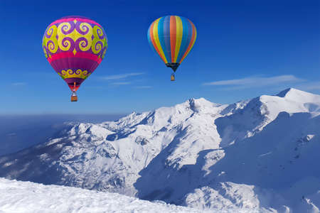 Colorful balloons flying over snow-covered mountains Stockfoto