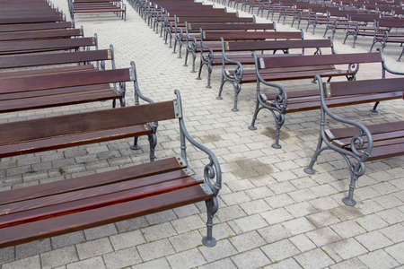 Lot of Rows of empty brown wooden benches Stockfoto