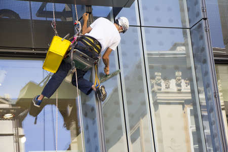 Window washer cleaning the windows of shopping center Stockfoto