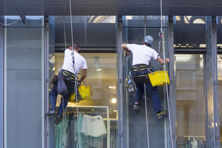 Window washers cleaning the windows of shopping center Stockfoto