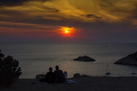 Ibiza, Young couple looking at the sea at sunset