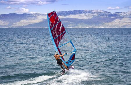 Young windsurfer in the waves in the sea Foto de archivo - 130798431