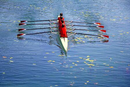 Czteroosobowa drużyna wioślarska mężczyzn na błękitnej wodzie, widok z góry