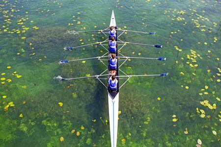 Men's quadruple rowing team on green water, top view Banco de Imagens