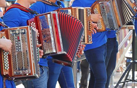 Group of young accordion players are playing in the town square
