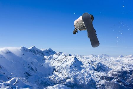Skier Snowboarder jumping through air with blue sky in background