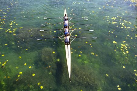Women's quadruple rowing team on turquoise green lake