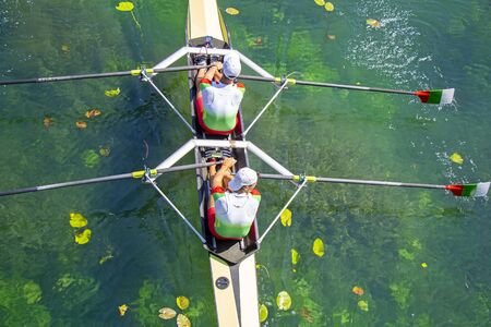 Two young athletes rowing team on turquoise green lake