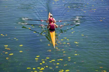 Équipe d'aviron de deux jeunes athlètes sur le lac vert turquoise