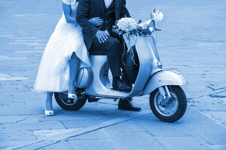 Young newlywed just married, posing on an old scooter. Classic Blue 2020 year color.