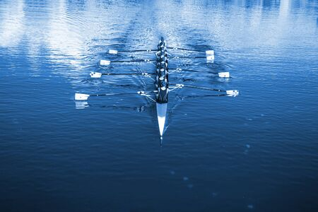 Barco tripulado ocho remeros remando en el tranquilo lago.