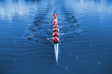 Boat coxed eight Rowers rowing on the blue lake. Foto de archivo