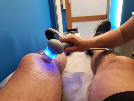 Physiotherapist is applying ultrasound therapy on the knee injury with ultrasound head transducer, blured motion