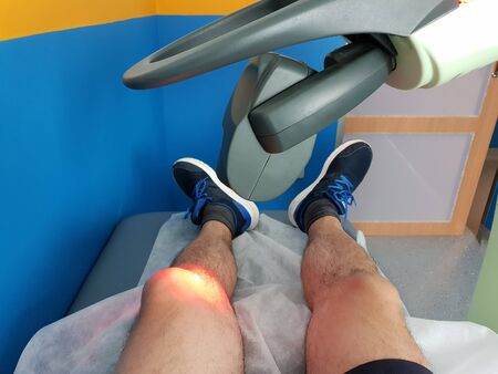 Physical therapy using a laser to treat an injured knee