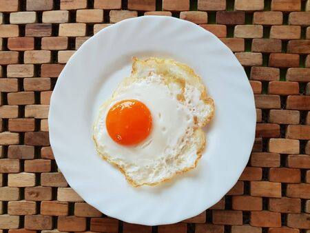 Fried egg on a white plate on a wooden background