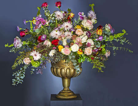 A Beautiful large flower bouquet with a lot of different flowers in a golden pot, on a blue background Stockfoto