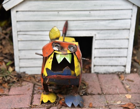 A cute colorful bull dog statue made from metal is defending his white dog house showing its vicious and large teeth Banco de Imagens