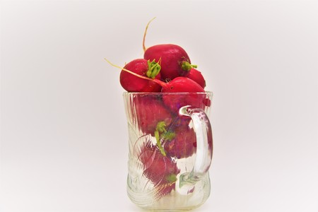 Eight healthy Red Radishes in a translucent coffee mug depicting a healthy drink Stock Photo