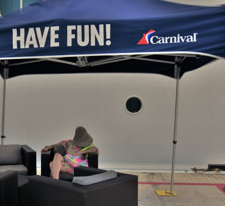 September 2018, Costa Maya, Mexico: A woman is taking a nap under Carnival Cruise Lines Have Fun sign depicting that perhaps she is a bored cruise passanger