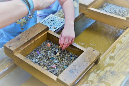 A photos showing a childs hand using a gold sifter panning for gold and gems a great educational outdoor acitivity with kids