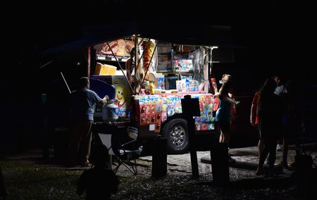 November 2018, Tampa, Ice Cream vendor in park in low light surrounded by customers