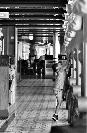 September 2018, Tampa, FL, USA - Black and White photo of an unsupervised child is playing inside the cruise ship dining area is creating a dangerous situation by risking fall injury as he is climbing
