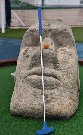 Blue tipped Minigolf putt and orange ball is resting on the nose of an easter island head in an authentic minigolf park Banque d'images - 114126284