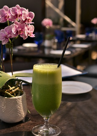 A healthy, tasty, beautiful green smoothie with a straw is served in a luxury hotel presented next to orchids Banque d'images - 114126285