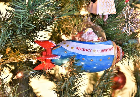 A photo of smiling Santa as tree ornament where he is riding a blue and white space ship rocket that says merry christmas depicting his arrival to town in a hurry to deliver presents. Banque d'images - 114126294