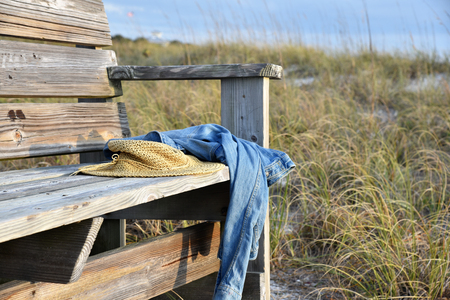A wide-brimmed hat and brown pillow rests on a wooden bench on sea sand beach on island with blured sea water,rock and trees background. Banque d'images - 115820815
