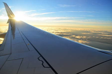 Wide angle view of airplane wing flying over the clouds with nice sun bokeh Banque d'images - 115820822